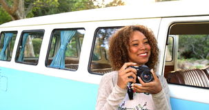 Woman taking a picture. In front of a van stock footage