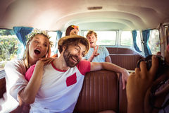 Woman taking a picture of her friends in campervan. In park royalty free stock images