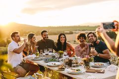Woman taking picture of her friends at dinner party royalty free stock images