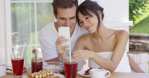 Woman taking picture of herself with husband. Smiling young woman taking picture of herself with attractive husband at table outside during breakfast time stock video
