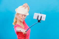 Woman taking picture of herself with phone on stick Royalty Free Stock Images