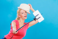 Woman taking picture of herself with phone on stick Stock Photos