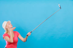 Woman taking picture of herself with phone on stick Royalty Free Stock Photography