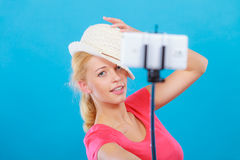 Woman taking picture of herself with phone on stick Royalty Free Stock Photos