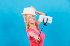 Woman taking picture of herself with phone on stick Stock Image