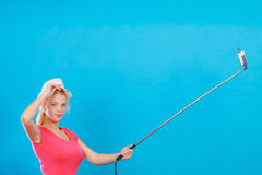 Woman taking picture of herself with phone on stick Stock Images