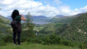 Woman taking picture of lake and mountains stock footage