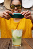 Woman taking picture of mojito with her mobile phone Royalty Free Stock Photos