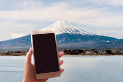 Woman taking a picture of Mount Fuji with a smart phone. Royalty Free Stock Photo
