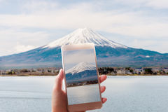 Woman taking a picture of Mount Fuji with a smart phone. Royalty Free Stock Photography
