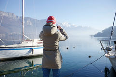 Woman taking picture of mountain lake Royalty Free Stock Image
