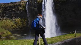 Woman taking picture of Seljalandsfoss watfall in Iceland stock video