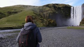 Woman taking picture of Seljalandsfoss watfall in Iceland. View of Seljalandsfoss watfall in Iceland stock footage