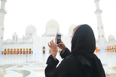 Woman taking picture of Sheikh Zayed Grand Mosque. By mobile phone stock image