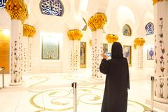 Woman taking picture of Sheikh Zayed Grand Mosque. By mobile phone stock photos