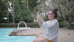 Woman taking picture in smart phone at resort swimming pool in the evening. stock video
