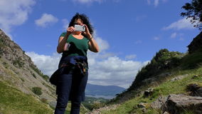 Woman taking picture with smartphone in mountains stock footage