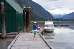 A woman taking a picture at the stewart yacht club. Stock Image