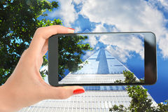 Woman taking a picture of a tall skyscraper in Manhattan New York with blue sky and clouds Stock Photography