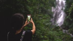 A woman is taking a picture of a waterfall stock video