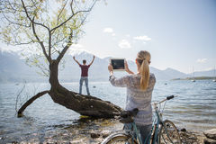 Woman taking pictures with digital tablet by the lake Royalty Free Stock Images