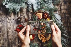 Woman taking pictures of glass bowl with Christmas mulled wine on wooden background. Woman taking pictures of of glass bowl with Christmas mulled wine and stock photography