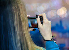 Woman taking pictures with her digital camera Stock Photography