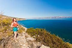 Woman taking pictures during holiday in Greece. Woman being on vacations taking pictures druing traveling. Female photographer photographing nature in Greece royalty free stock photo