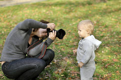 Woman taking pictures of a little boy Royalty Free Stock Images