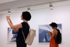Women at photo exhition using smartphones, mobile devices and social network addiction royalty free stock photo