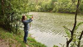 Woman taking pictures on the river bank Stock Photography