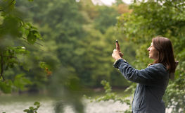 Woman taking pictures on the river bank Stock Photo
