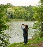 Woman taking pictures on the river bank Royalty Free Stock Photos
