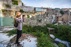 Woman taking pictures of ruins abandoned buildings. Royalty Free Stock Photos