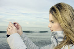 Young woman taking picture of North Sea Stock Photo