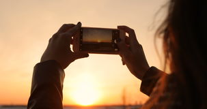 A woman is taking pictures of a sunset on a smartphone
