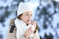 Woman taking a pill in a cold snowy winter Royalty Free Stock Image
