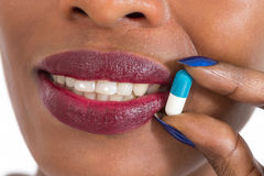 Woman taking pills. Close up of mouth and tablet between finger Stock Photos