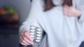 Woman taking pills medicine against heart attack. Woman person take pills medicine on kitchen has unexpected sudden chest pain ache stethalgia sharp heart attack stock footage
