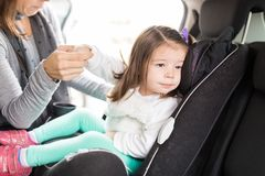 Woman Taking Precautions For Daughter In Car. Cropped image of caring mother adjusting car seat for little daughter stock image