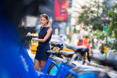 Woman taking public city  bicycle Royalty Free Stock Photo