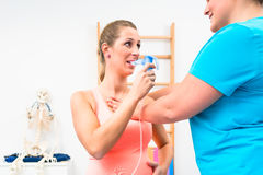 Woman taking pulmonary function test with mouthpiece in her hand. Woman helped by physiotherapist taking pulmonary function test with mouthpiece in her hand royalty free stock images