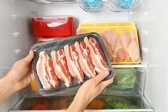 Woman taking raw bacon from refrigerator. Closeup stock images
