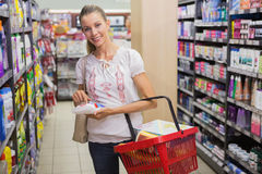 Woman taking a rice bag in the shelf of aisle Royalty Free Stock Images