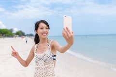 Woman taking sefie with cellphone in sand beach Royalty Free Stock Photo