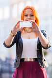 Woman taking self picture with smartphone camera Royalty Free Stock Photography