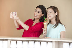 Woman Taking Self Portrait With Daughter Holding Chocolate Ice. Happy mid adult women taking self portrait with daughter holding chocolate ice cream at parlor Stock Images