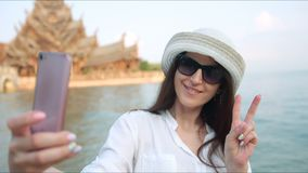 Woman taking self-portrait photo in front of the ancient temple. Girl on summer vacation visiting famous asia tourist. Destination having fun and smiling stock video footage