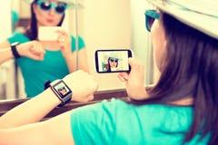 Woman taking self portrait selfie photo. Smartwatch concept. Woman taking self portrait selfie photo and sends it to smartwatch stock photo