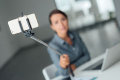 Woman taking a self portrait using a selfie stick Royalty Free Stock Images